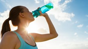 lady drinking water from a reusable sport bottle